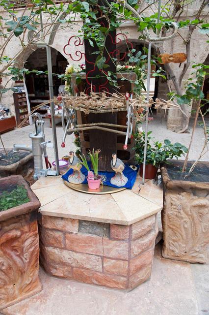 Скульптуры куропаток на колодце центральной монастырской цистерны посреди двора
